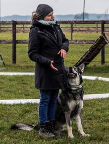 Anna und Logan beim Training Das Bild zeigt Anna Wolf und Ihren Hund Logan beim Training. Anna erklärt gestenreich Ihren Schüler eine übung. Ihr Hund Logan sitz vorbildlich links neben ihr und schaut punktgenau auf sein Frauchen